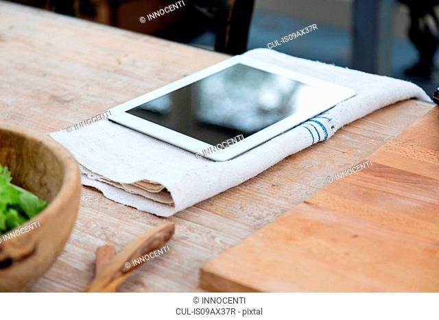 Digital tablet on tea towel on wooden surface