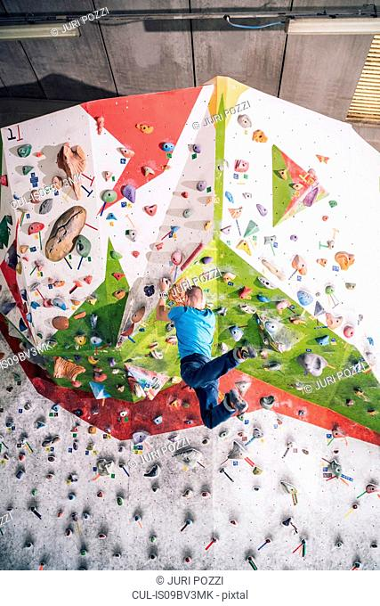 Climber dangling from climbing wall