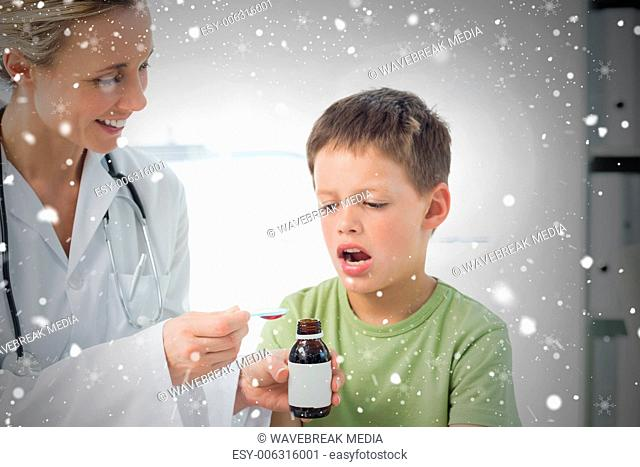 Doctor giving little boy cough syrup