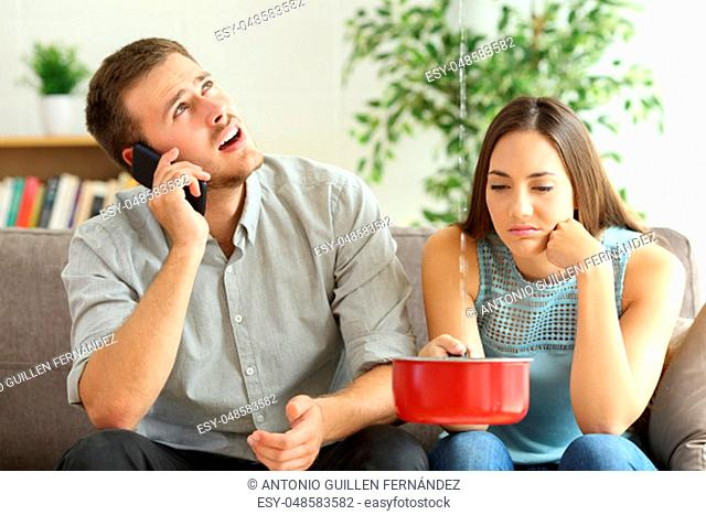 Upset couple sitting in a couch in the living room and calling insurance for home leaks