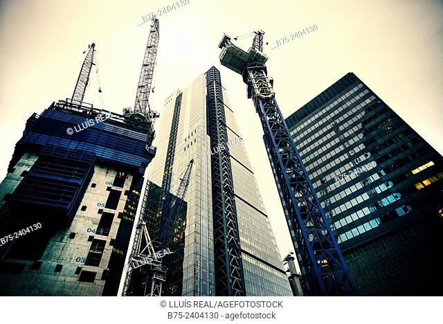 A building under construction and cranes, The Cheesegrater building and another office building of modern architecture in Bishopsgate, City of London, England