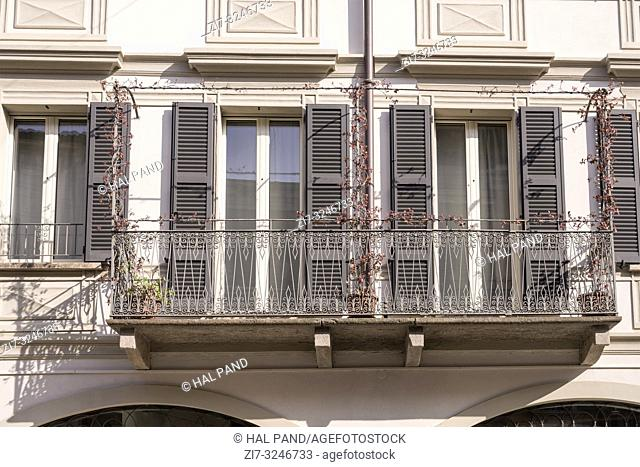 detail of old balcony in city center with art wrought iron railing , shot in bright winter light at Cremona, Lombardy, Italy