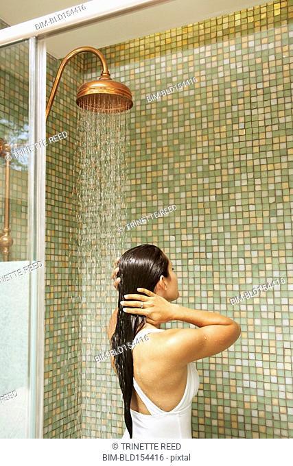 Hispanic woman showering in bathing suit