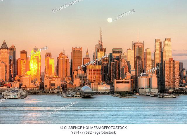 The waxing gibbous moon rises over the New York City skyline the day before the full moon, as the setting sun in the west reflects off the windows and facades...