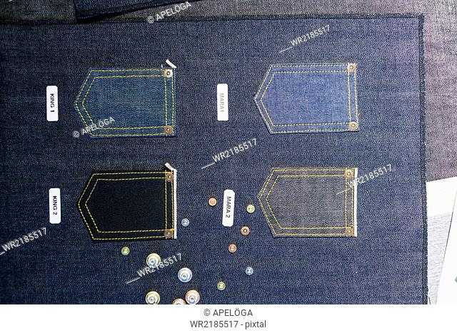 Buttons and pockets on denim fabric in factory