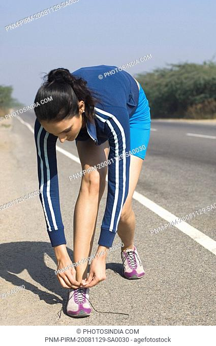 Woman tying her shoelace at the roadside