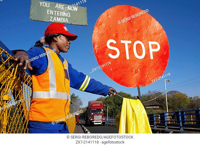 A woman controls the traffic between Zambia and Zimbabwe. A STOP sign indicates that we are entering Zambia. Today one of the Victoria Falls Bridge's main...