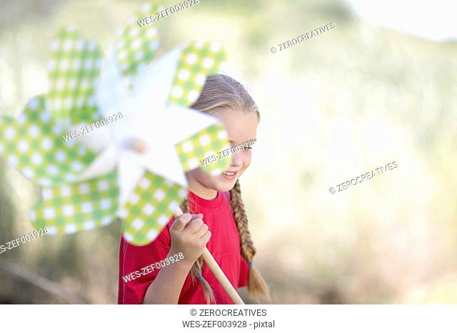 South Africa, Girl on field trip playing with paper wind wheel