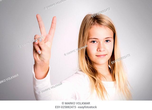 nice blond girl in front of gray background showing victory sign