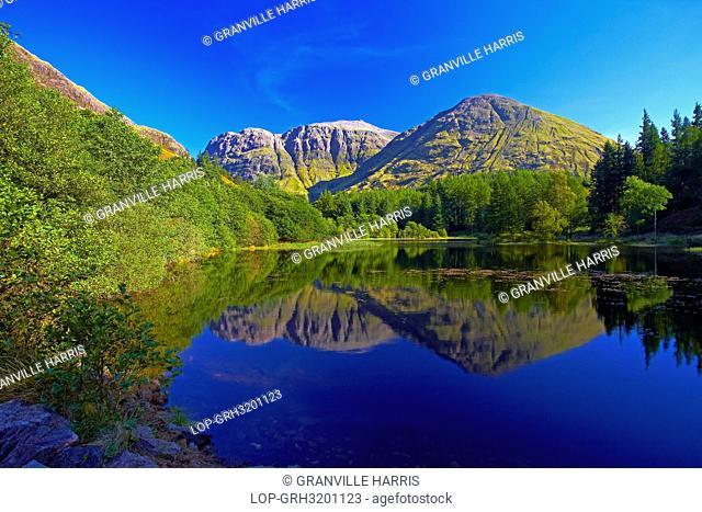 Scotland, Highland, Glen Coe. Aonach Dubh, one of the Three Sisters of Glen Coe reflected in the still water of Torren Lochan