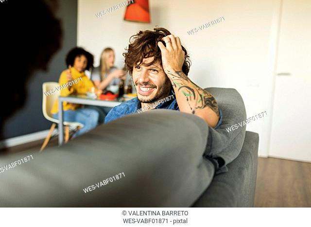 Happy couple sitting on couch talking with friends in background