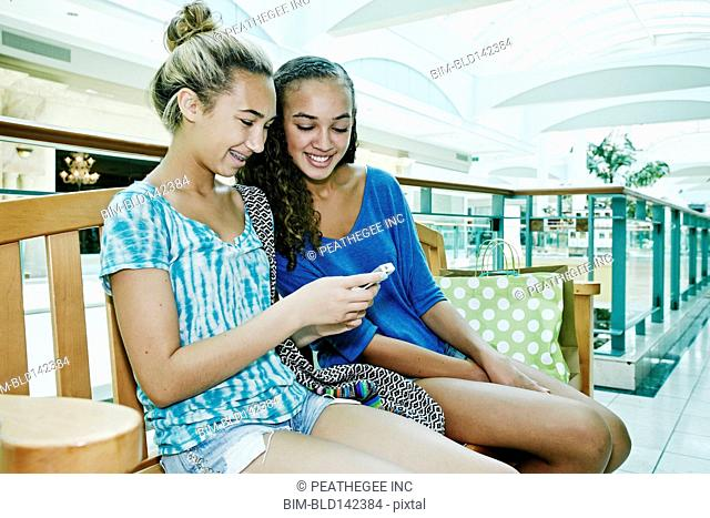 Mixed race teenage girls using cell phone together at shopping mall