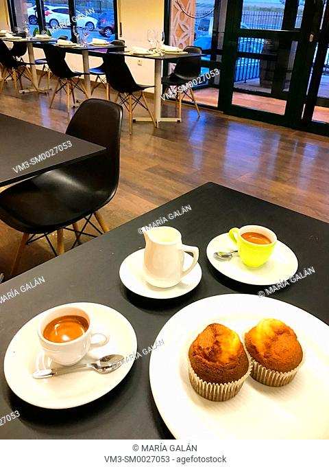 Two cups of coffee and muffins in a cafeteria. Spain