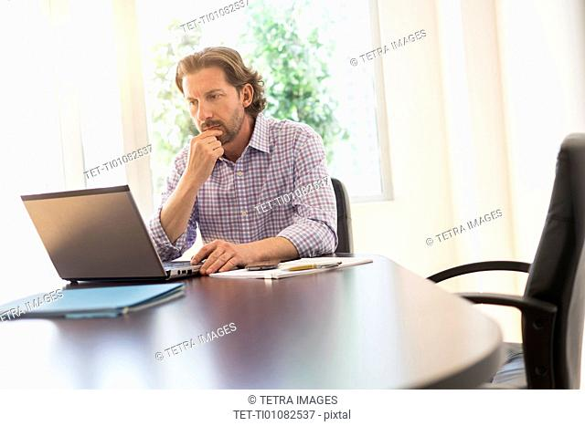 Businessman using laptop at table