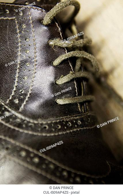 Close up of leather brogue and shoelaces in shoe makers workshop
