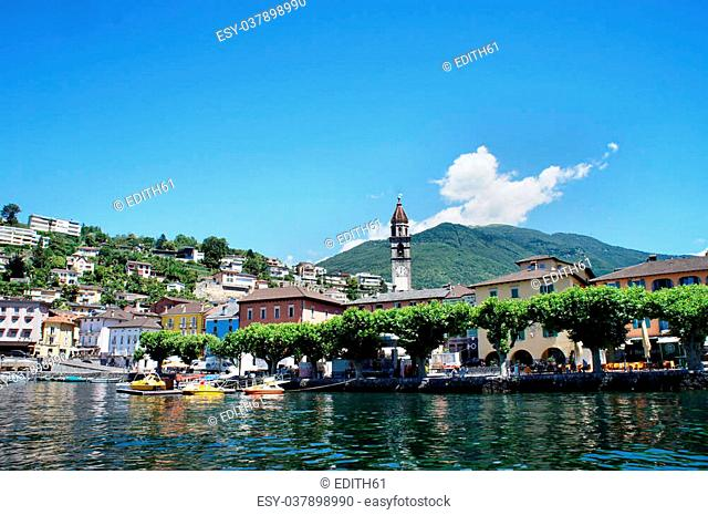 View from Lake Maggiore on Ascona in the canton of Ticino in Switzerland; houses and a church tower; green plan trees on the shore, blue sky and a white clouds