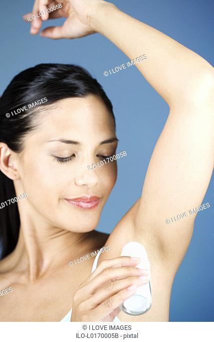 A young woman applying a de-odorant