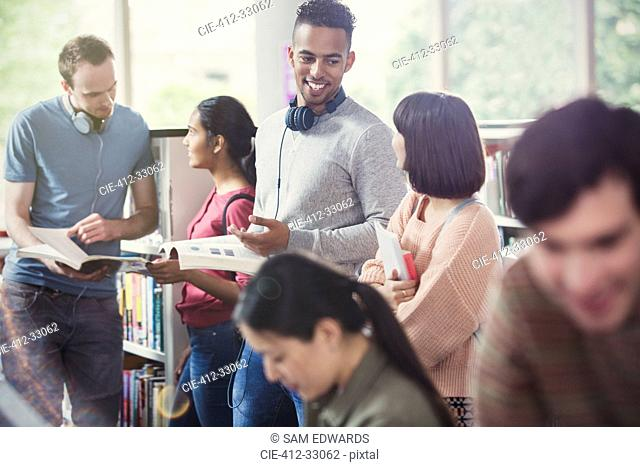 College students talking and studying in library