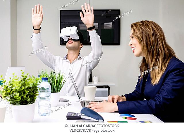 Side view of young laughing girl sitting with laptop at table with man in VR headset gesturing