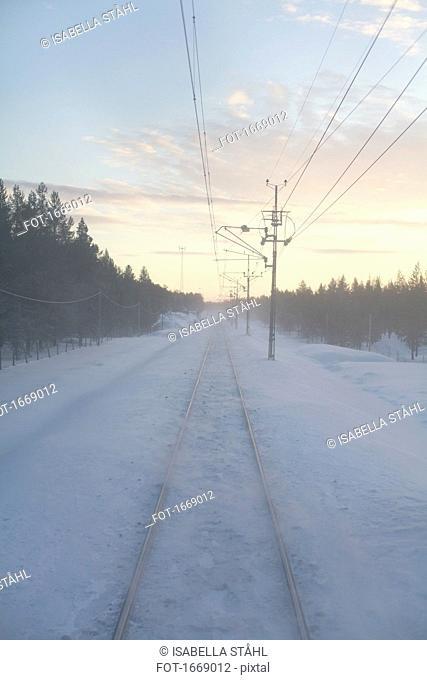 Snow covered railroad track by electricity pylons amidst trees during sunset, Kiruna, Sweden