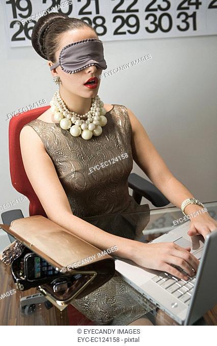Cheerful young woman wearing eye mask, using laptop