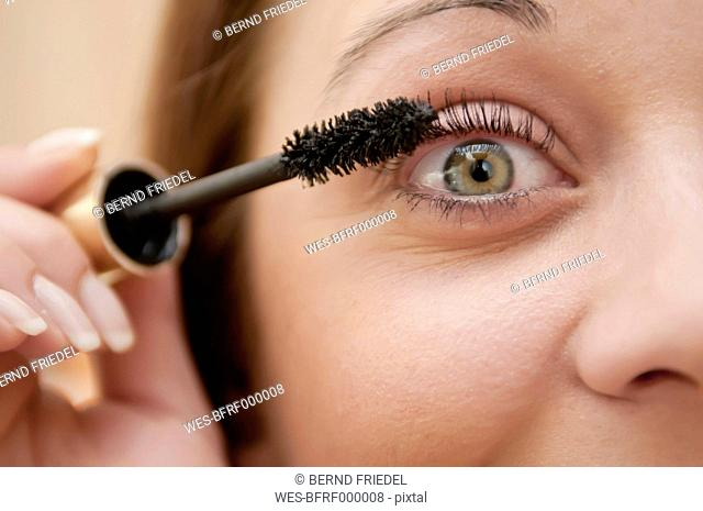 Germany, Berlin, Young woman applying mascara, close up