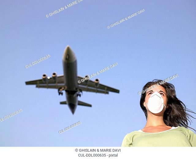 Woman wearing a surgical mask while a plane flies overhead
