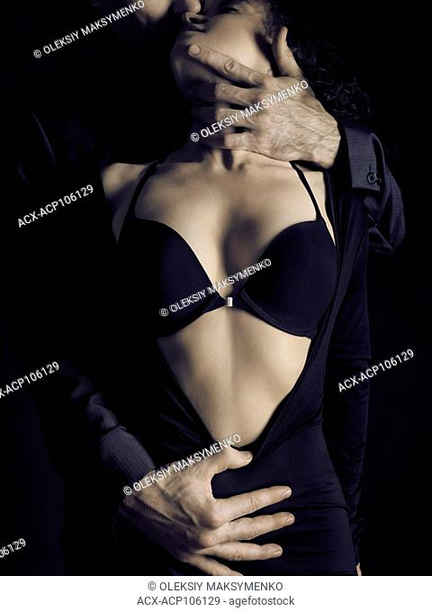 Artistic sensual portrait of a couple, a man caressing a beautiful woman in a black bra and undone black dress revealing her chest