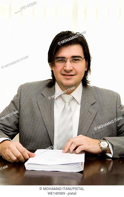 Young business man sitting in office with report