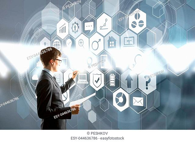 Side view of handsome young european businessman drawing glowing business interface on blurry background. Future and success concept. Double exposure