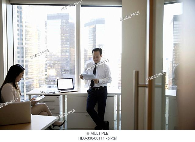 Businessman and businesswoman using digital tablet and reading paperwork in highrise office