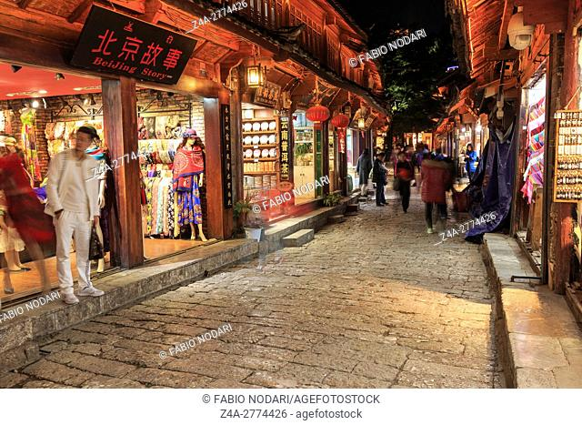 Panoramic view of one of the streets in Lijiang Old Town at sunset with some tourists passing by