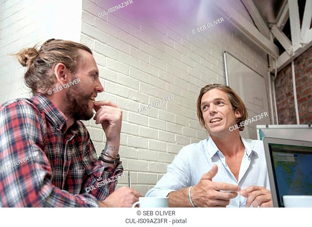 Two men having meeting in creative studio