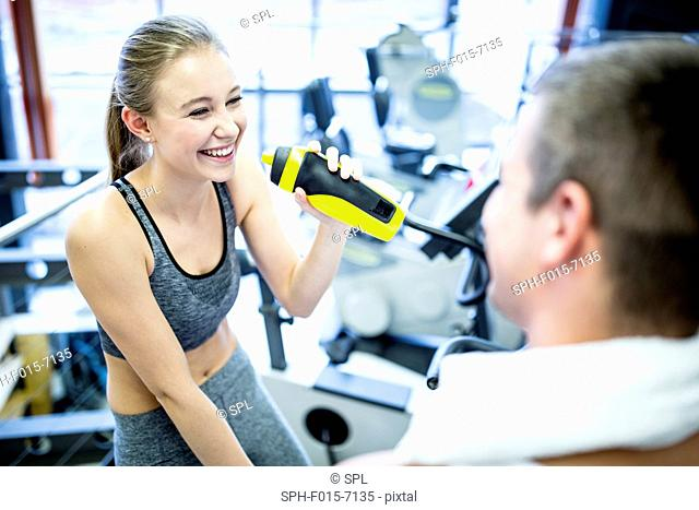 MODEL RELEASED. Young woman drinking water in gym, smiling