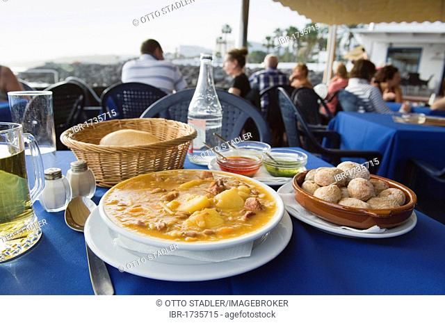 Spanish food in the restaurant, vegetable soup with Canarian potatoes, Papas Arrugadas, Souce Mojo Rojo, Mojo Verde, Lanzarote, Canary Islands, Spain, Europe