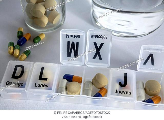 Pills with pill organizer, writing in Spanish