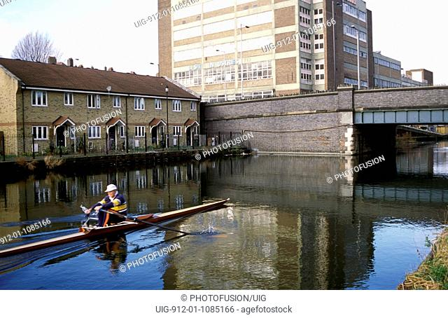 Rowing on River Lea Navigation with matchbox factory & new housing in background East London UK