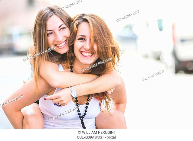 Young woman giving girlfriend piggyback ride in street