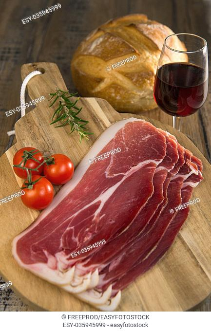 Cured pork meat or prosciutto on a rustic wooden board with tomatoes and bread, France