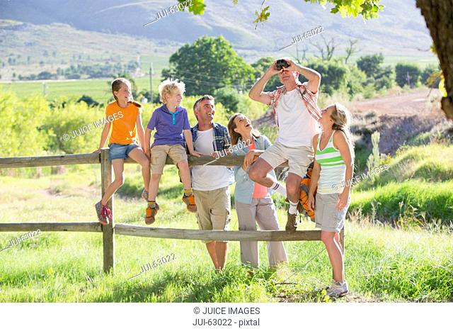Multi generation family resting on a fence in a rural setting