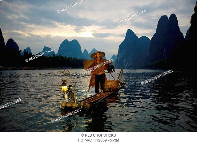 Senior man standing on a bamboo raft in a river with a hill range in the background, Guilin Hills, XingPing, Yangshuo, Guangxi Province, China