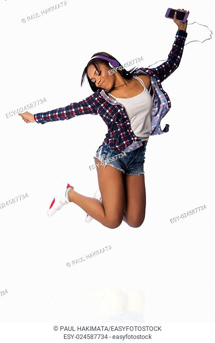 Beautiful happy teenager jumping dancing jamming listening to music, on white