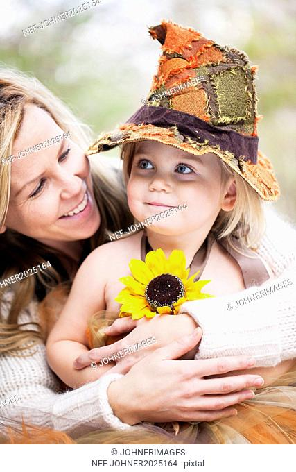 Smiling girl wearing witch hat with mother