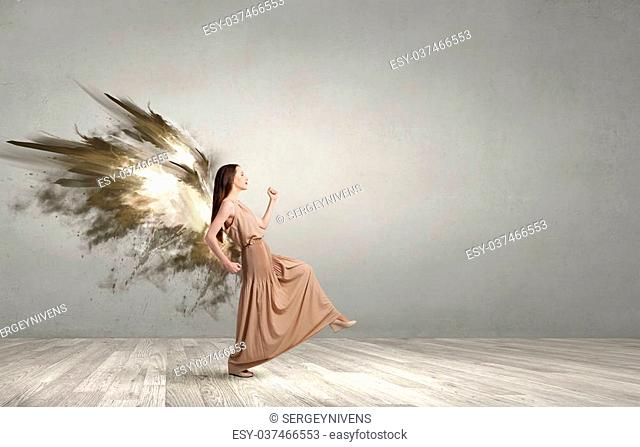Attractive woman with angel wings in empty room