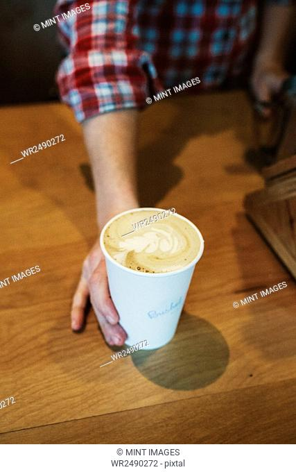 A person putting a cup of freshly made coffee with froth and fern pattern on the surface on a wooden counter