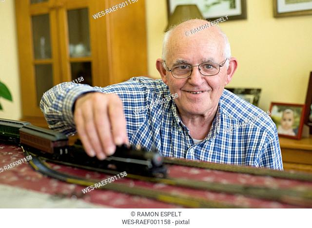 Portrait of smiling senior man with his model railway