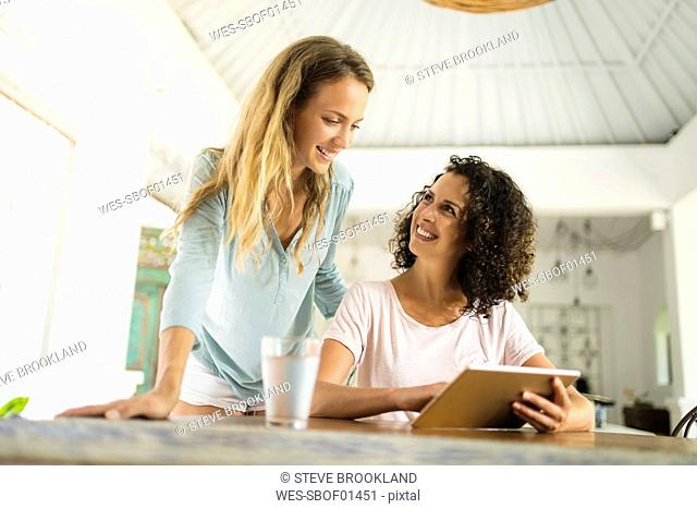 Two smiling women at home using tablet