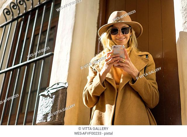 Fashionable young woman at house entrance using cell phone