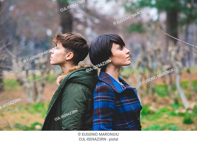 Two young women standing back to back in rural setting