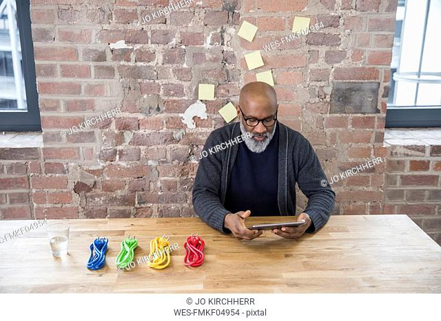 Businessman with tablet and coloured power cables at wooden table